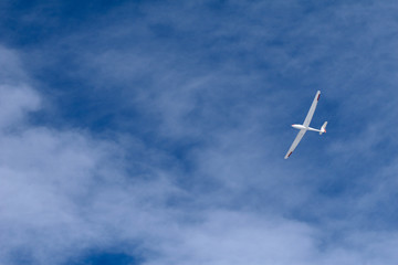 A glider flying across the blue sky