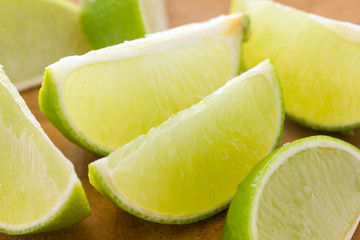 Lime wedges arranged on a wooden board. Selective focus.