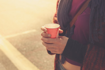 Young woman is standing in the street with a cup