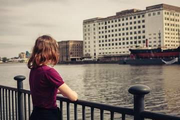 Young woman relaxing by river and looking across at buildings