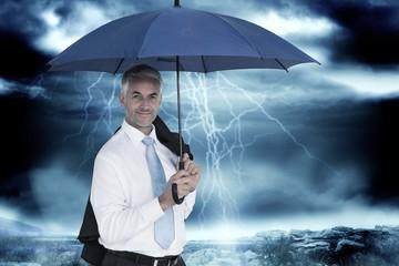 Composite image of businessman holding blue umbrella
