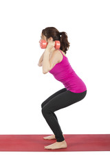 Fitness woman in squat pose with dumbbells