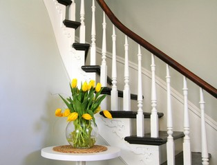Yellow tulips on a round table beside heritage staircase