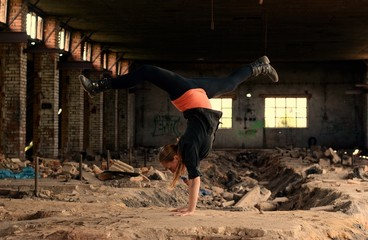 Teenager dancing breakdance in the old brickworks