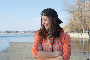 Girl smiling and listening music in baseball cap at the lake