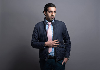 Contemporary fashion man wearing blue jacket and pink tie. Black