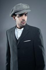 Mafia fashion man wearing grey striped suit with cap. Black hair