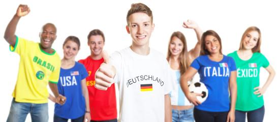 Blonder deutscher Fussball Fan zeigt Daumen mit anderen Fans
