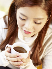 young woman holding cup of coffee high angle view