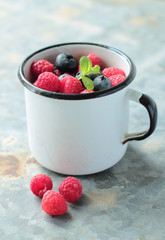 Old tin mug with blueberry and raspberry fruits