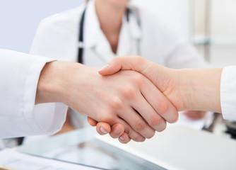 Doctors Shaking Hands At Desk