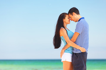 Young couple kissing on the beach in summer day.