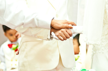 Goom holds bride's hand in wedding day