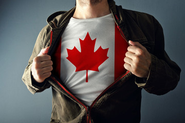 Papiers peints Canada Man stretching jacket to reveal shirt with Canada flag