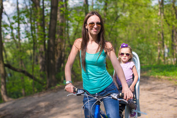 Young mother and cute little daughter riding bikes together