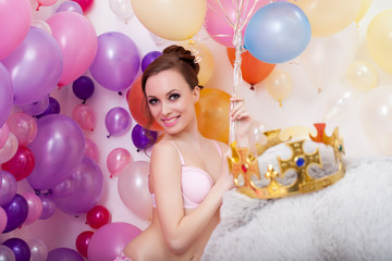 Smiling young woman posing with bunch of balloons