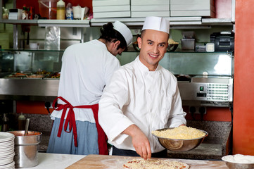 Young chef making pizza at kitchen