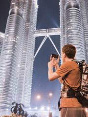 Young man photographs two famous Petronas Twin Towers