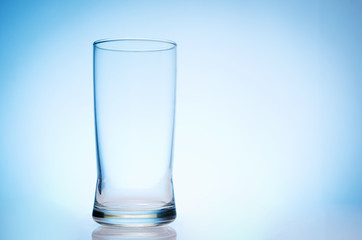 tall empty glass of water on bluebackground