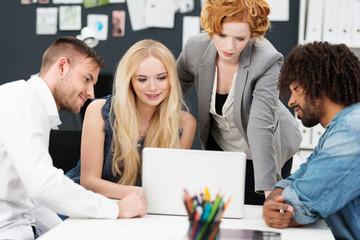 kreatives team schaut sich einen entwurf am laptop an