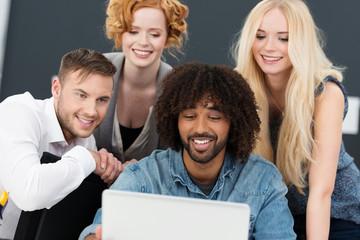 vier studenten schauen auf notebook