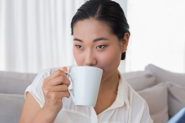 Smiling woman sitting on couch having coffee