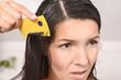 Frau kämmt Läuse aus ihrem Haar