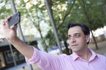 Man taking self portrait with mobile phone