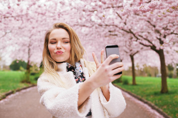 Cute young woman at spring blossom park taking self portrait