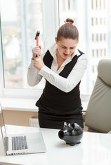 angry woman at office hitting piggy bank with hammer