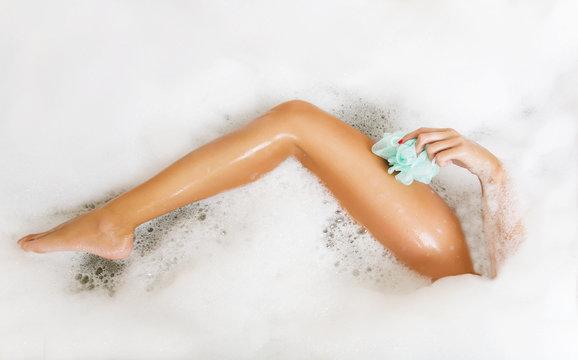 Woman in bath washing leg in bathtub