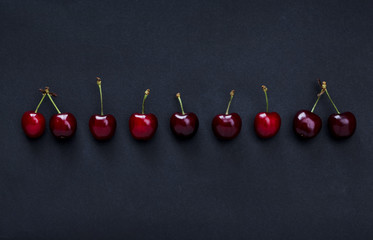 Red cherries on black background