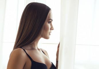 beautiful woman with dark hair looking at window