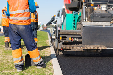 Tracked paver machine and construction workers during road works