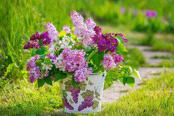 Beautiful bouquet of lilac in the decoupage decorated bucket