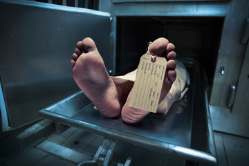 Feet on a morgue table with toe tag with dramatic lighting