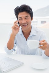 Smiling man having coffee and talking on phone