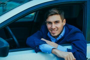 Smiling handsome businessman sitting in car. Smile