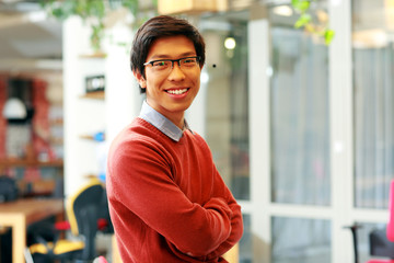 handsome asian man with arms folded standing in office