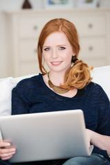 elegante junge frau mit laptop auf dem sofa