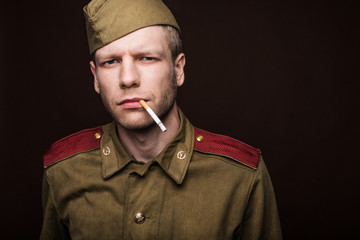 Russian soldier smoking cigarette and looks at something
