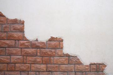 Cracked White wall with orange brick