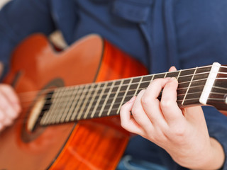 woman plays on classical acoustic guitar