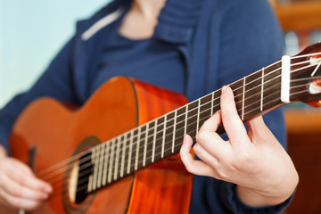 girl playing classical acoustic guitar