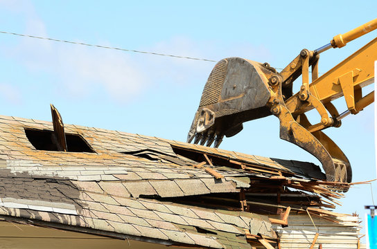 A large track hoe excavator tearing down an old hotel to make wa