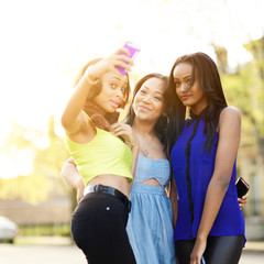 group of three girls wearing bright clothes taking selfies