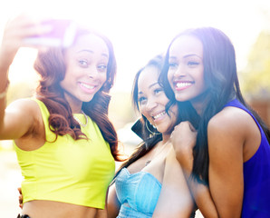 three african girls taking selfies with smart phone
