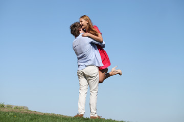 Young happy couple on blue sky