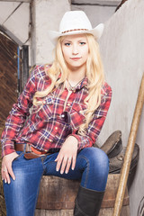 Caucasian Cowgirl In Stetson Sitting on Barrel on the Farm