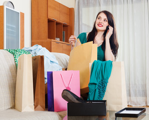 woman looking purchases and speaking by mobile
